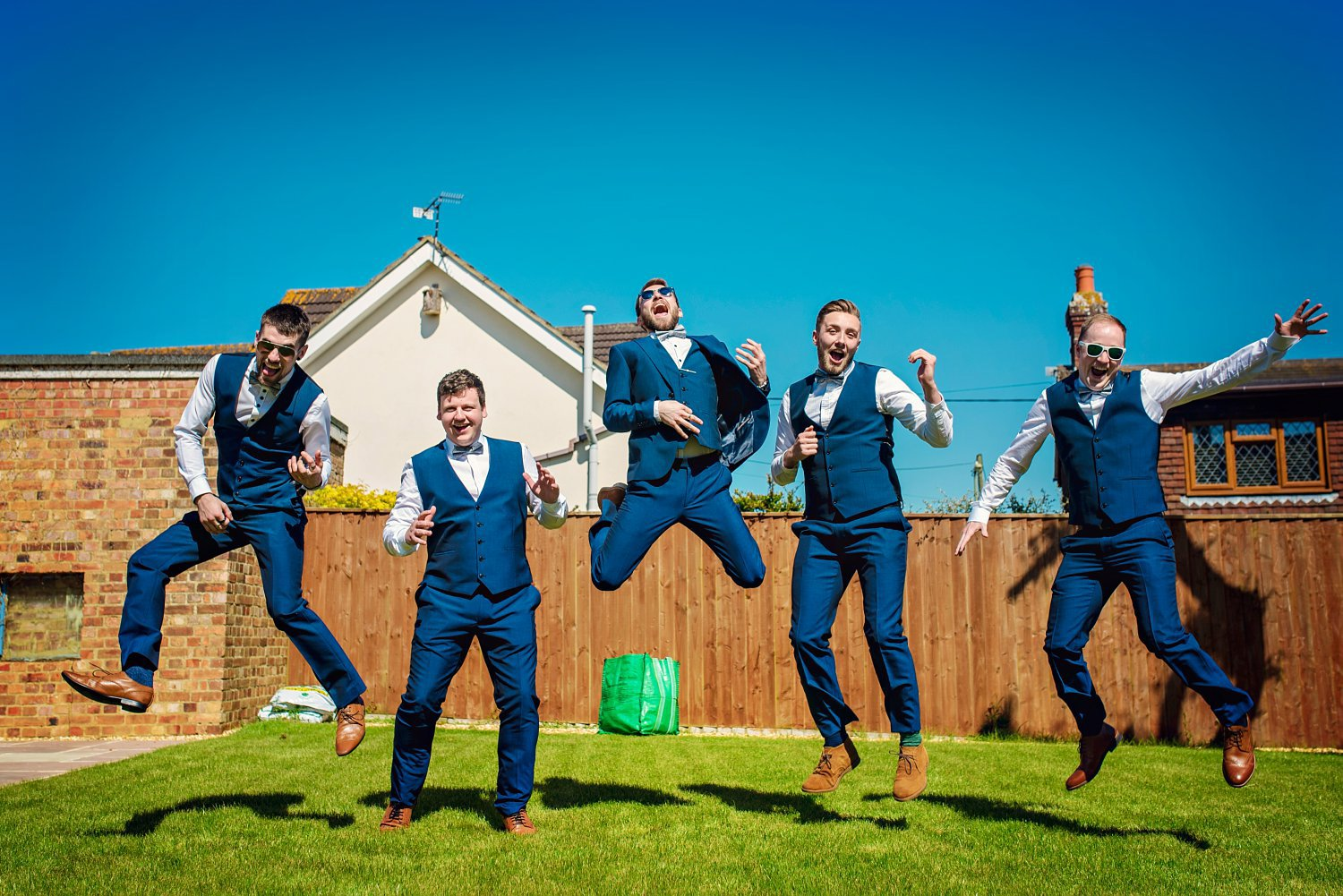 group photo of the groom and his groomsmen. they are all jumping except one groomsman