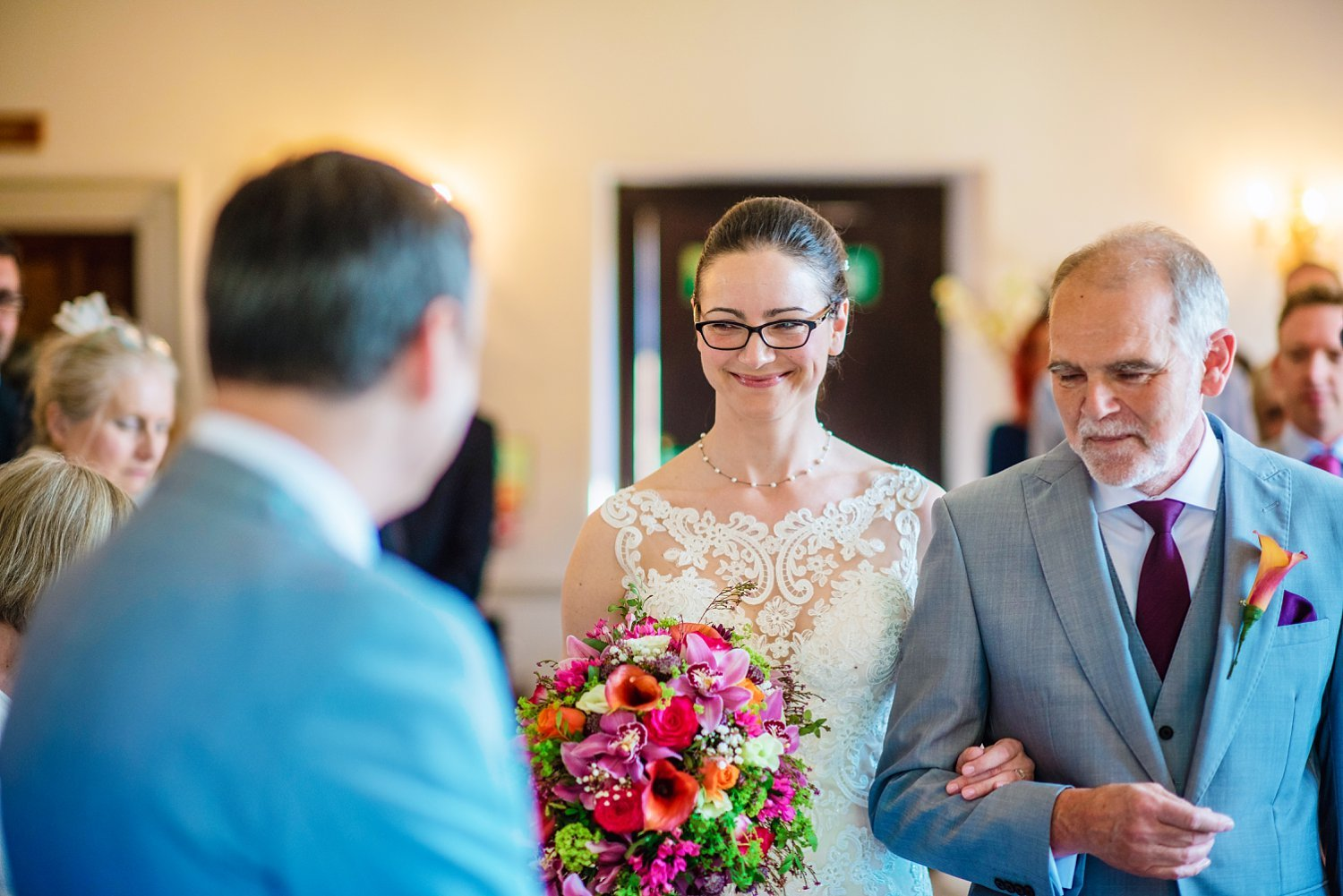 New Place Hotel Wedding - bride smiling at her husband to be as she is walking down the aisle