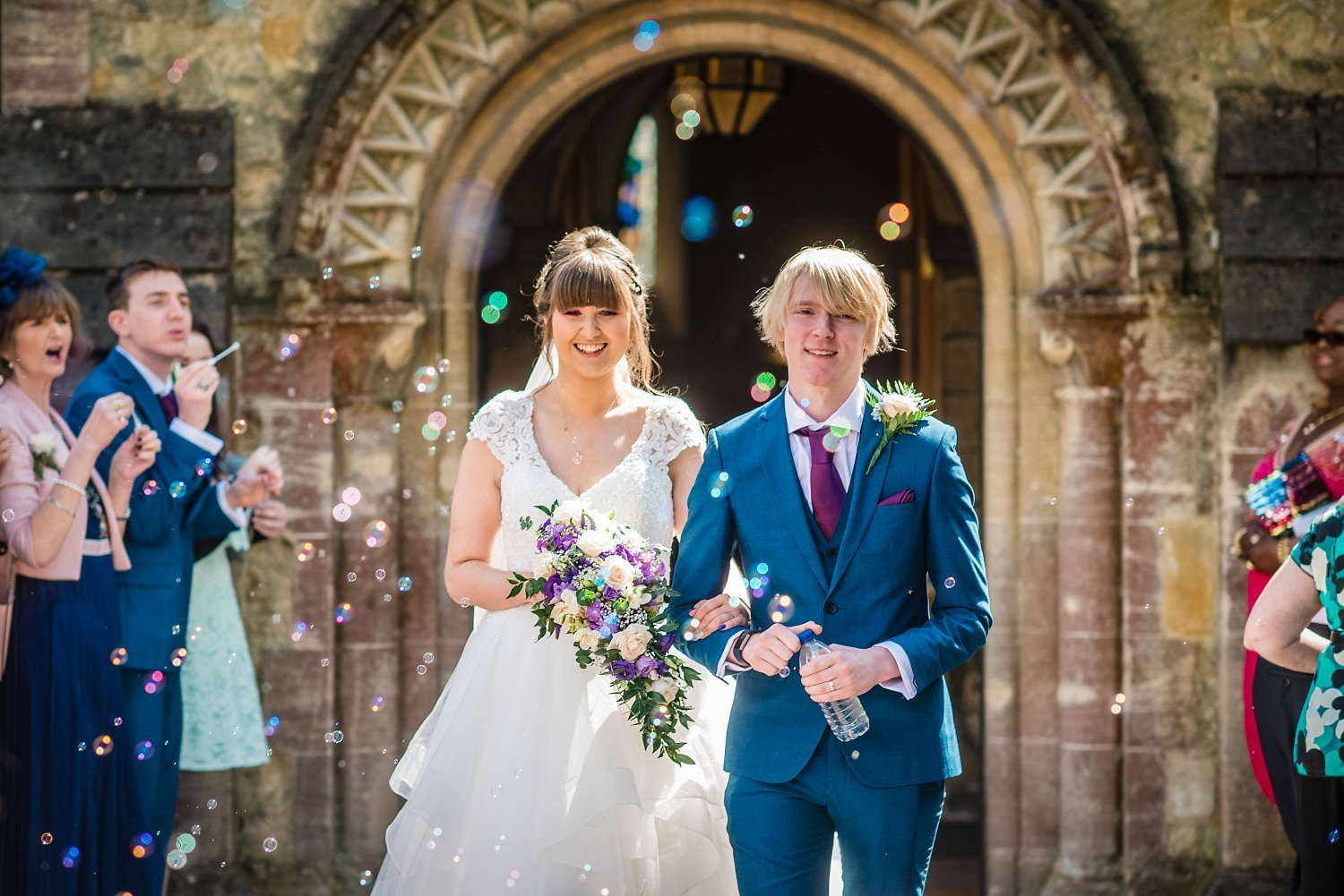 bride and groom walking down whilst wedding guests are blowing bubbles - Petersfield wedding photography