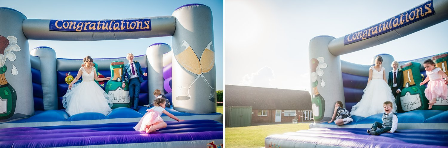 bride and groom playing on the bouncy castle