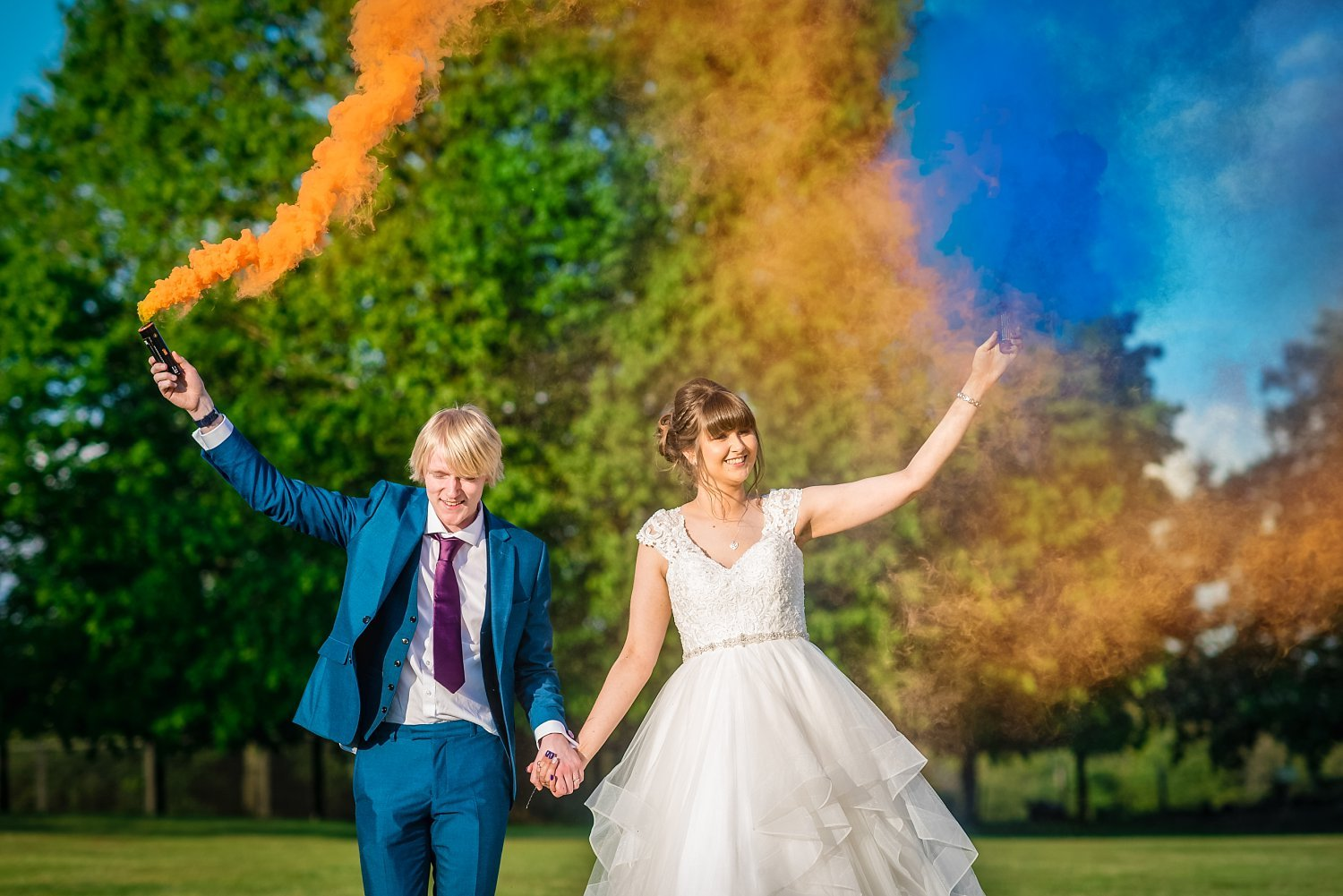 bride and groom are holding hands. they hold a smoke bomb each- smoke bombs produce yellow and blue smoke - Petersfield Wedding Photography