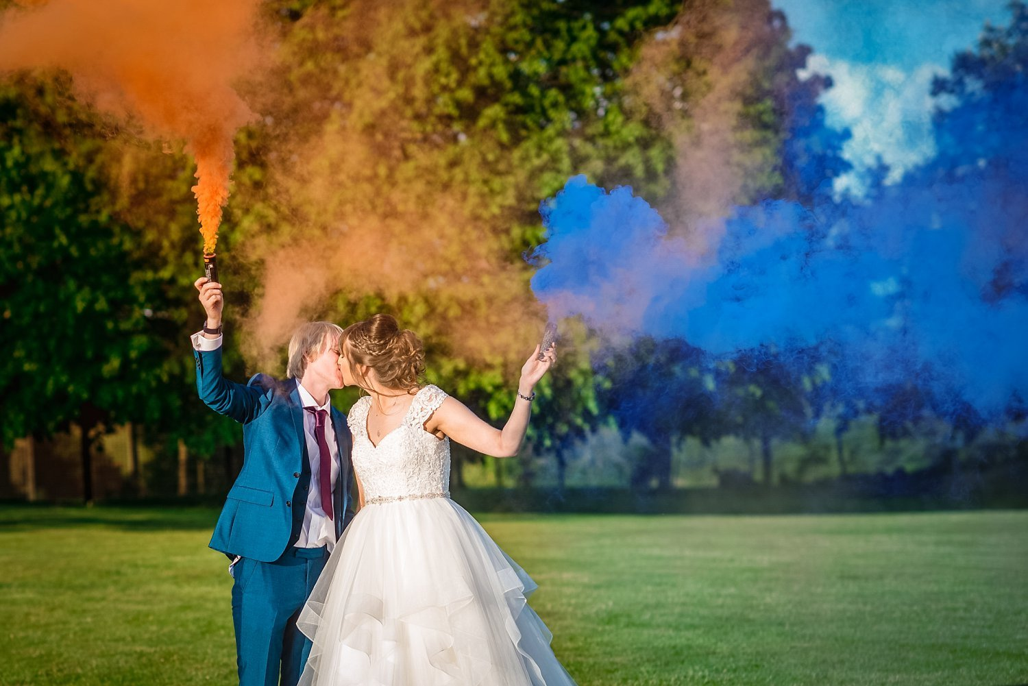 bride and groom are having a kiss, they hold blue and orange smoke bombs - Petersfield Wedding Photography