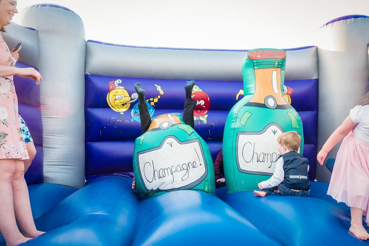 a wedding guest fell over on the bouncy castle. you can see his feet up in the air - Petersfield Wedding Photography