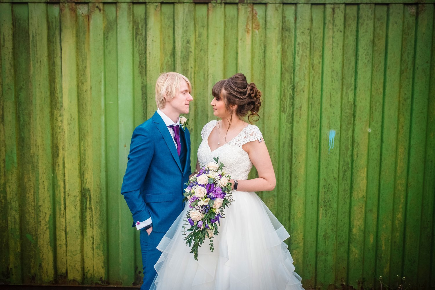 bride and groom in front of greenish container - Petersfield Wedding Photography