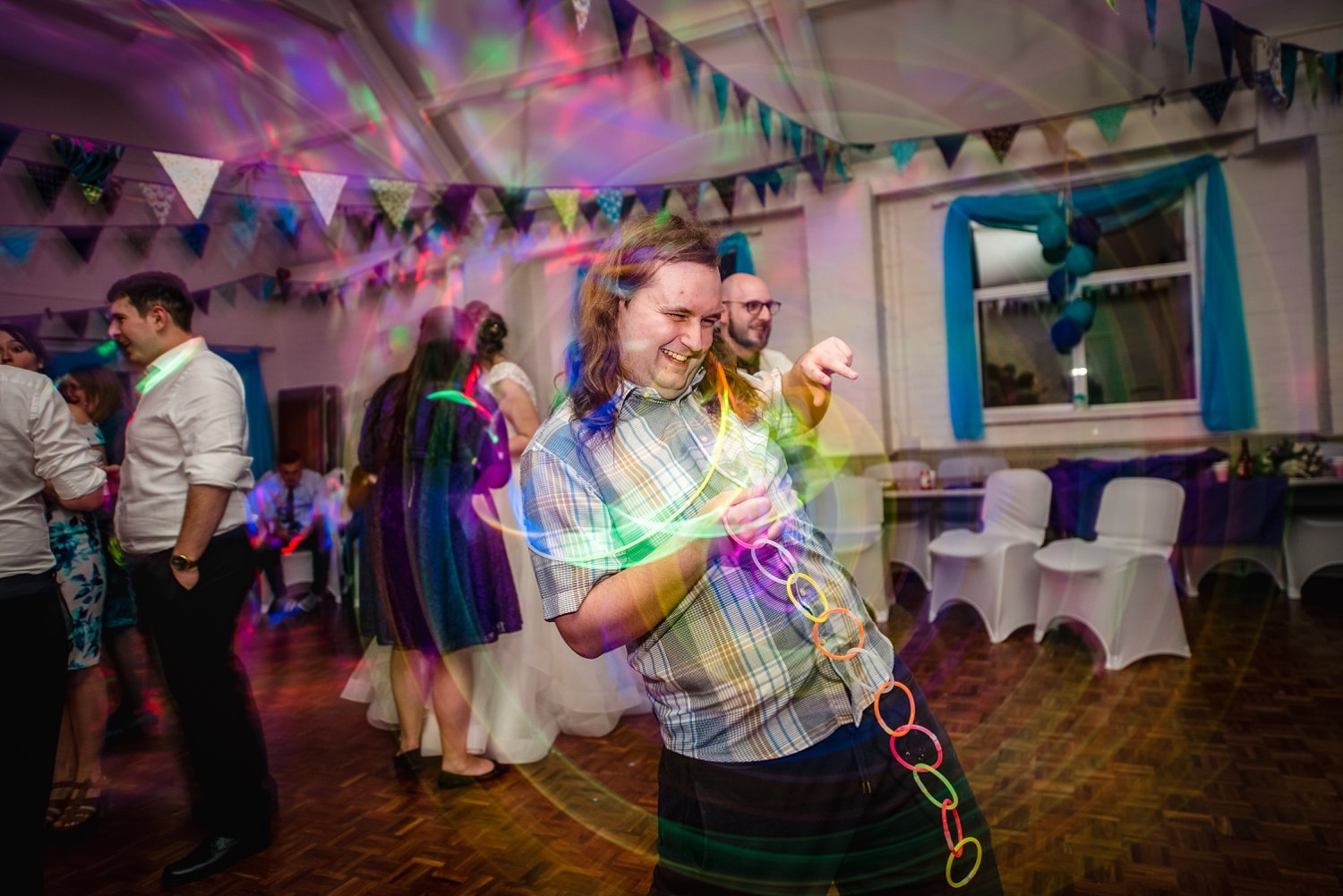 party time, wedding guest is dancing, glow sticks leave a trails of colourful light - Petersfield Wedding Photography