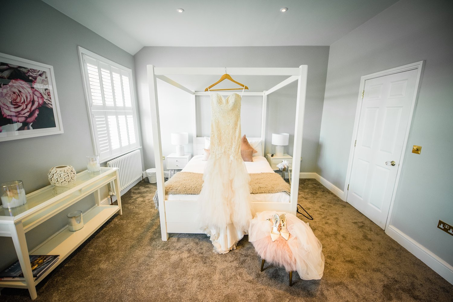 Northbrook Park Wedding - photo of the wedding dress and shoes. Dress is hanged on the top frame of the bed