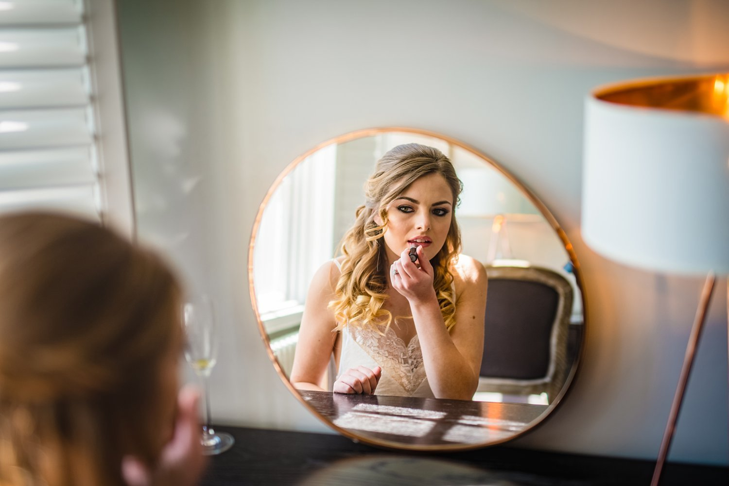 Northbrook Park Wedding - bride is putting lipstick on in fron of the mirror