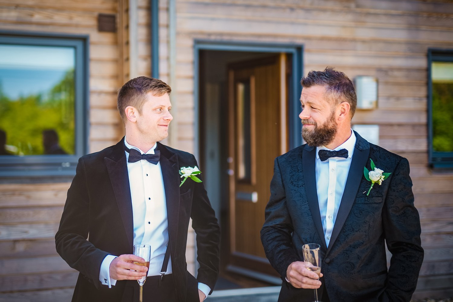 Northbrook Park Wedding - groom and father of the bride are looking at each other, smiling. they both hold a glass of champagne in their hand