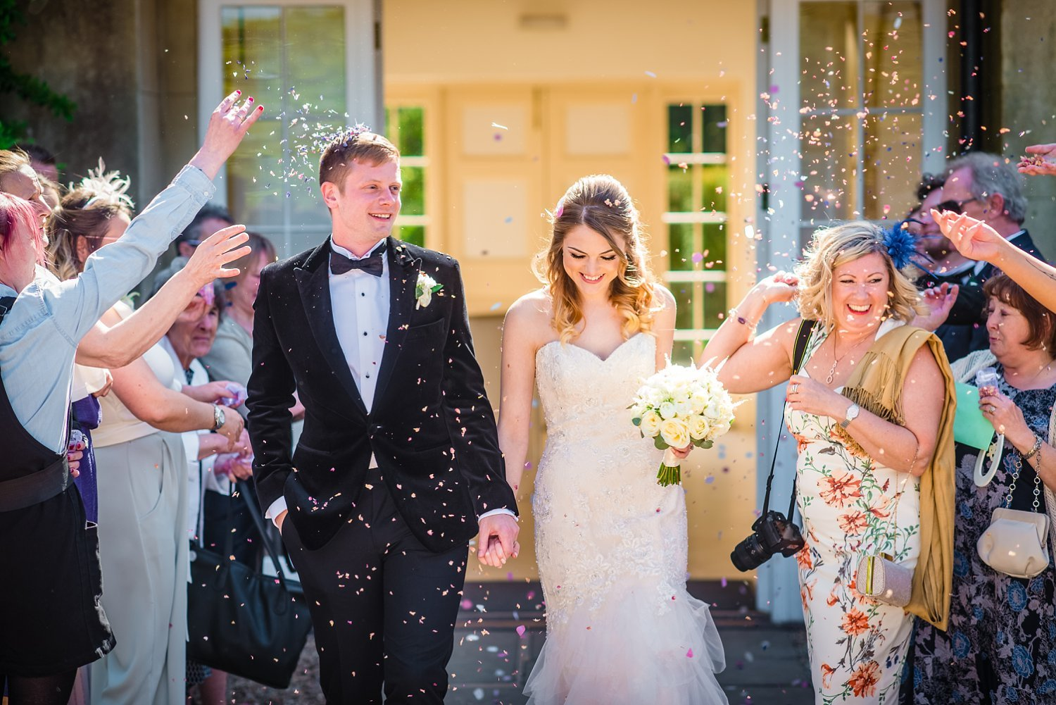 Northbrook Park Wedding - confetti photo. bride and groom are walking as their guests throw confetti at them