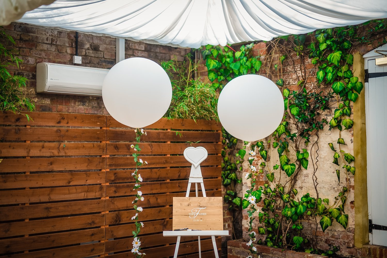 Northbrook Park Wedding - wooden frame with name of the bride and groom. their wedding guests can write a little message on it (congratulating them). there are too big white baloons on each side