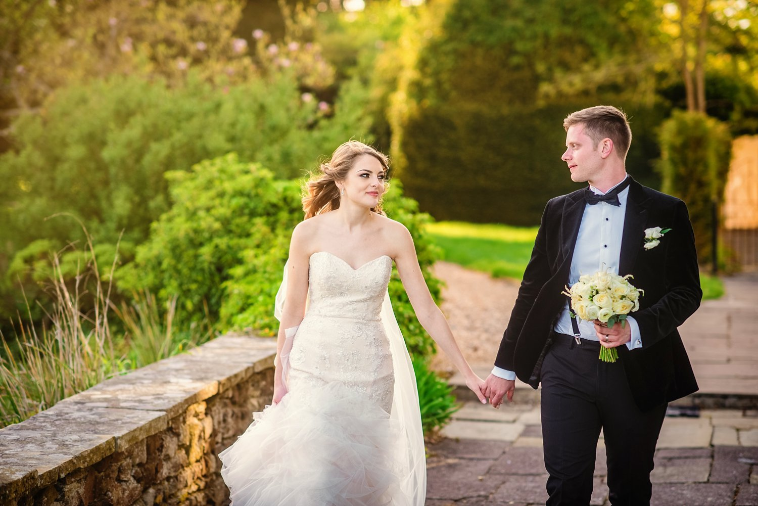 Northbrook Park Wedding - bride and groom are walking, holding hands and looking at each other