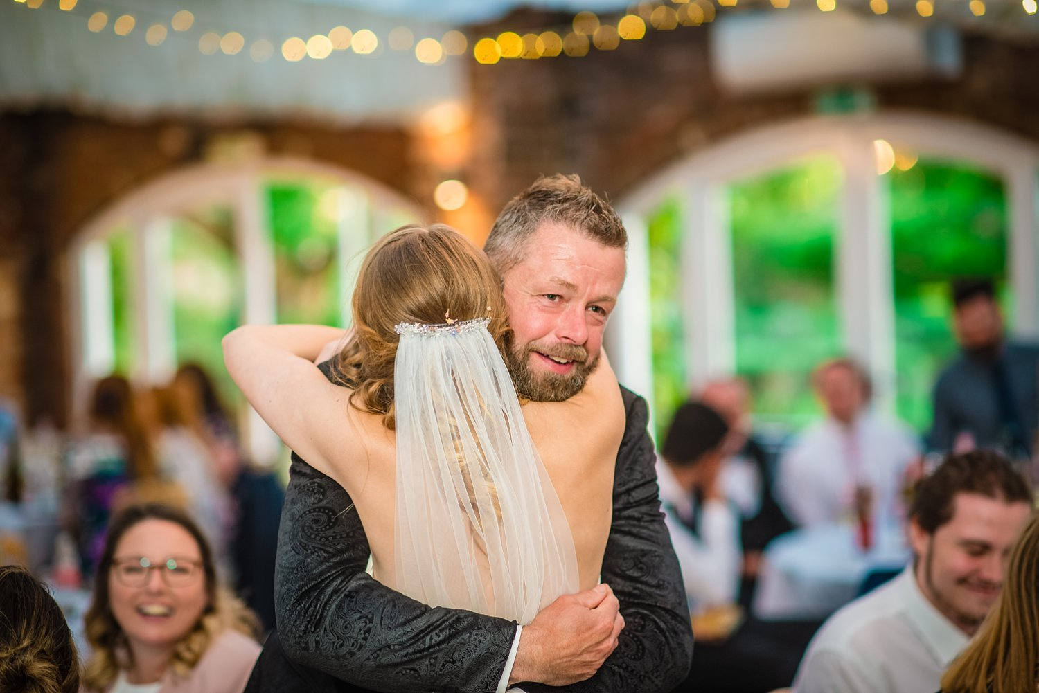 Northbrook Park Wedding - bride and groom are having a hug. you can see dad's smiling