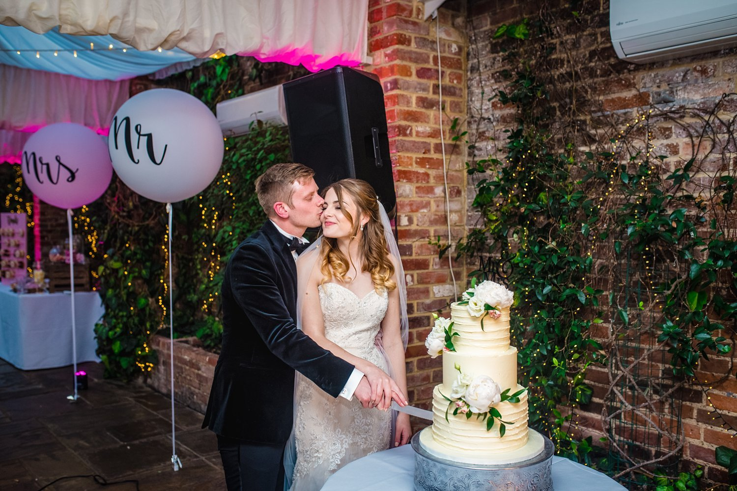Northbrook Park Wedding - bride and groom are cutting a cake. husband gives her wife a kiss on a cheek