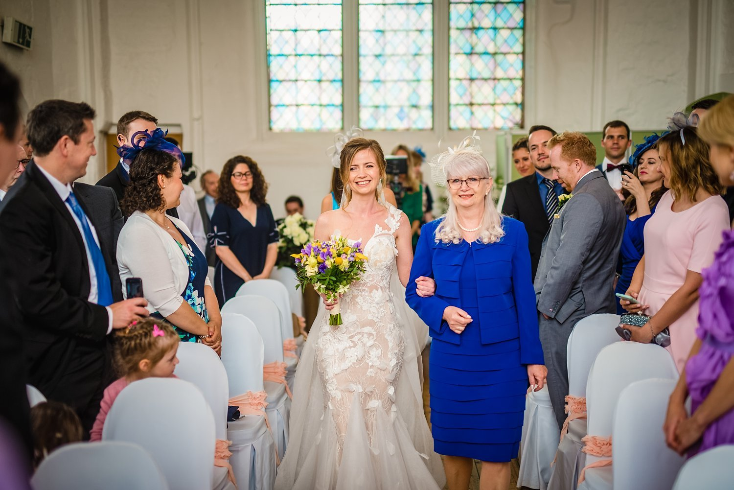 Fun-Filled wedding in Pembroke Lodge - bride and mother of the bride are walking down the aisle