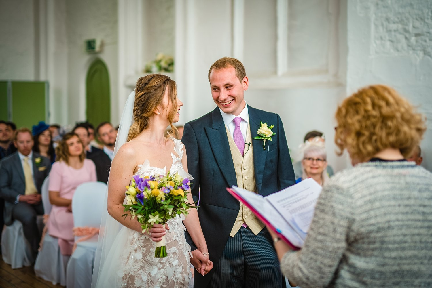 Fun-Filled wedding in Pembroke Lodge - groom is smiling. he is holding bride's hand
