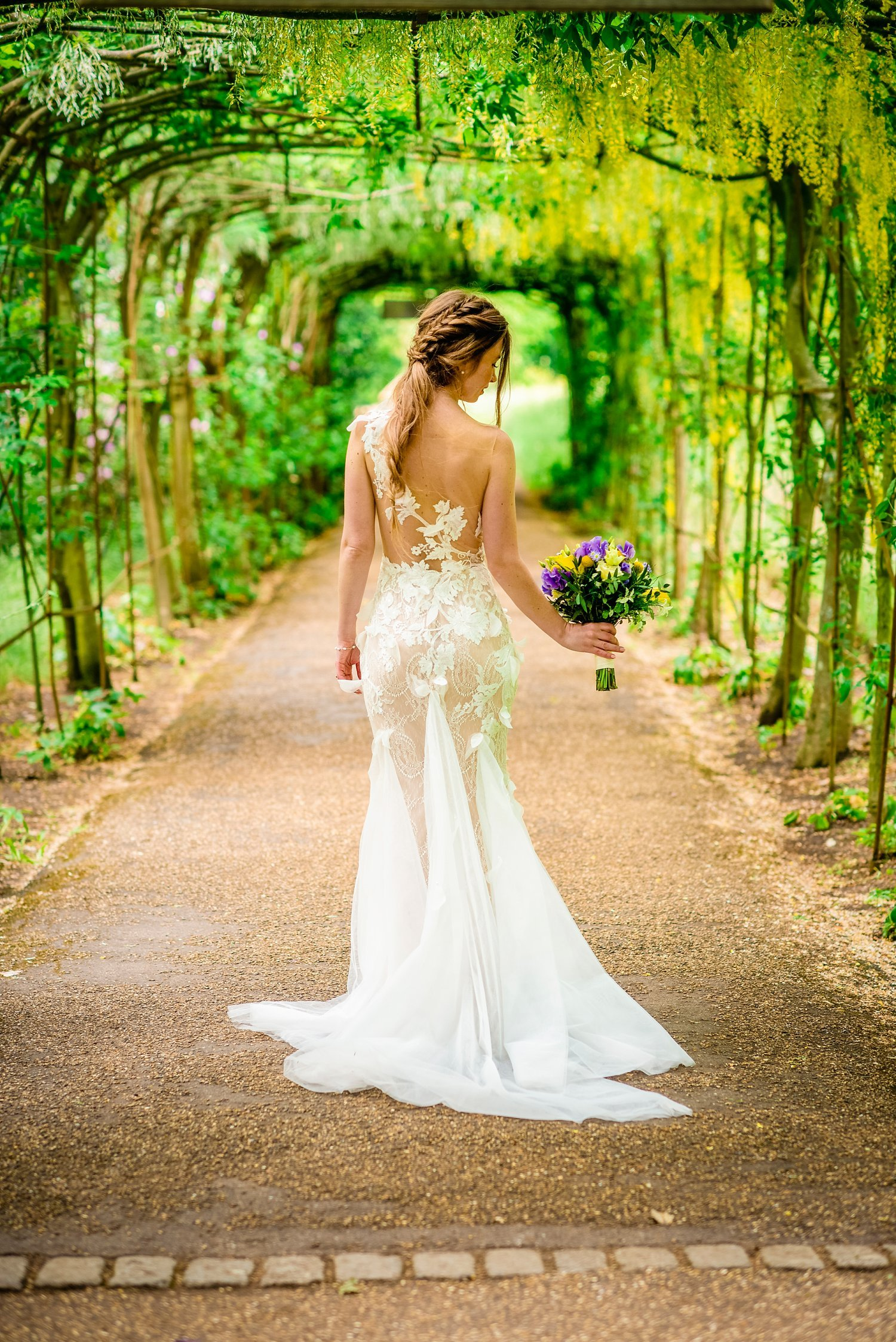Fun-Filled wedding in Pembroke Lodge - photo of the back of bride's dress. bride is looking down at her flowers