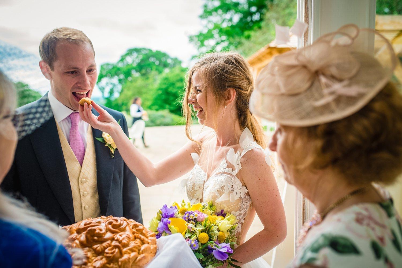 Fun-Filled wedding in Pembroke Lodge - groom is eating bread