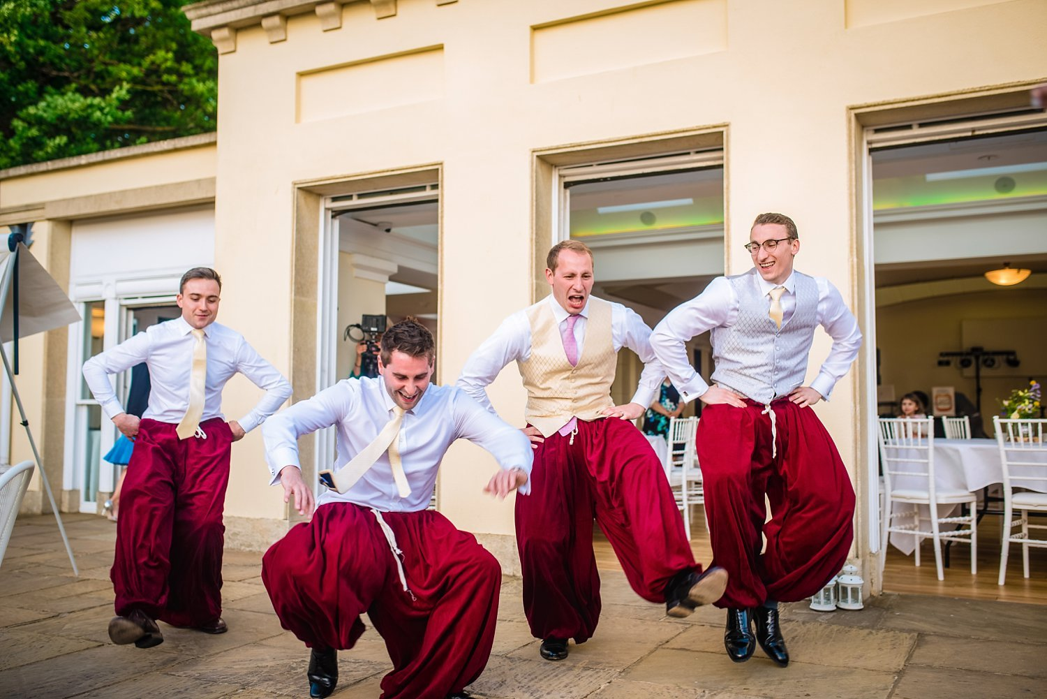Fun-Filled wedding in Pembroke Lodge - groom and groomsmen are dancing, they are wearing traditional ukrainian trousers