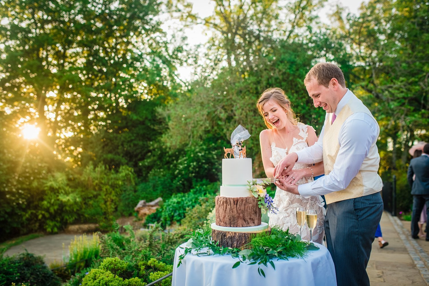 Fun-Filled wedding in Pembroke Lodge - bride and groom are cutting a cake outside