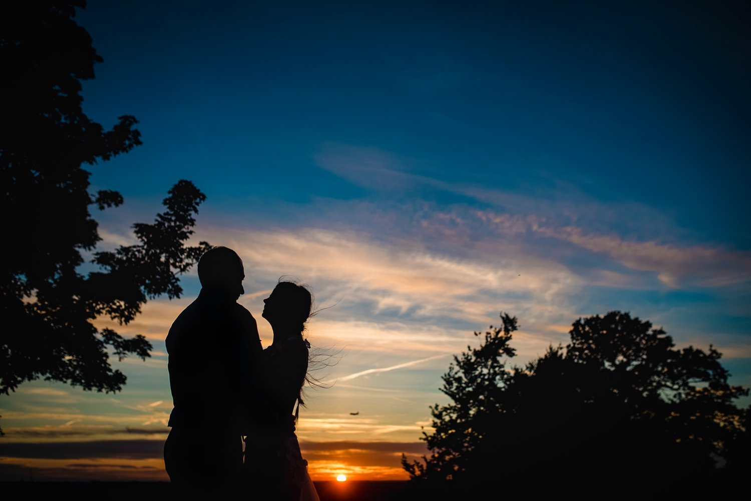 Fun-Filled wedding in Pembroke Lodge - silhouette of bride and groom during sunset