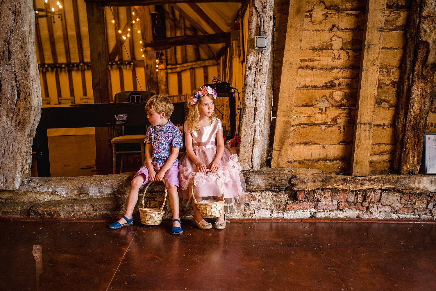 Colville Hall Weding Photographer-page boy and girl sat down on a wood plank in the ceremony room