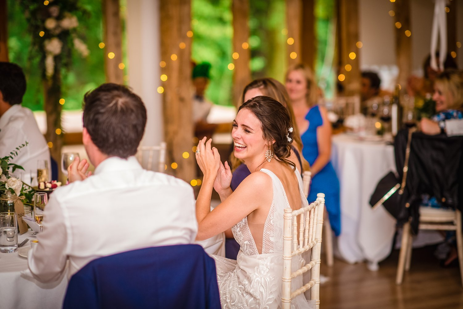 Colville Hall Weding Photographer-bride is laughinhg sat down at the table
