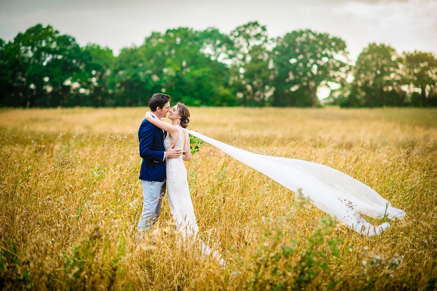 Colville Hall Weding Photographer-bride and groom are cuddling in the field.