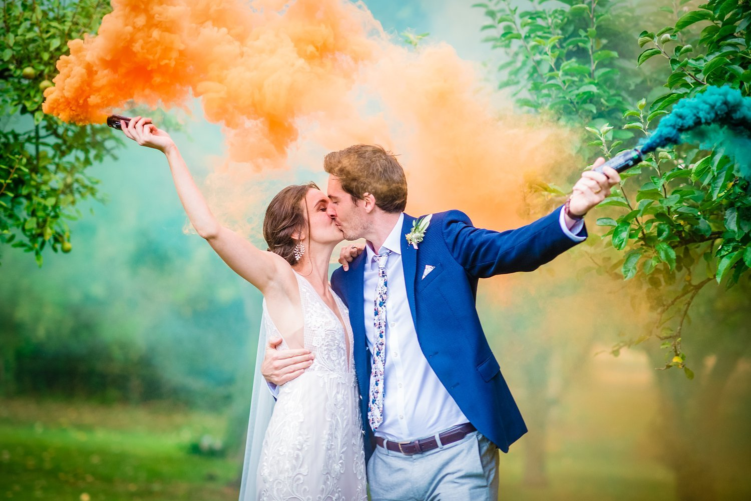 Colville Hall Weding Photographer - bride and groom are having a kiss. they are holding an orange and blue smoke bomb