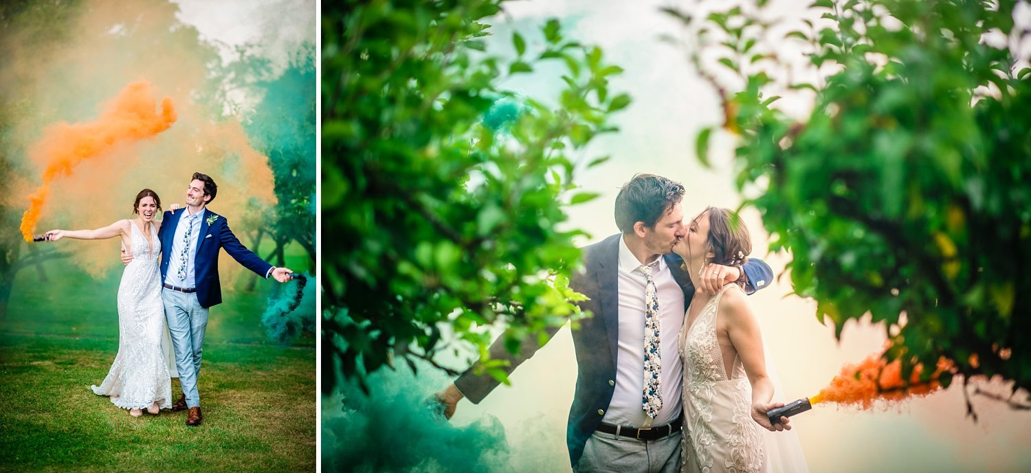 Colville Hall Weding Photographer - bride and groom are having a kiss. they are holding smoke bombs