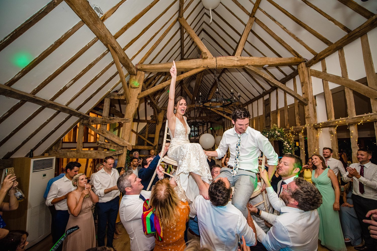 Colville Hall Weding Photographer - bride groom are picked up by wedding guests. they are high up in air on chair