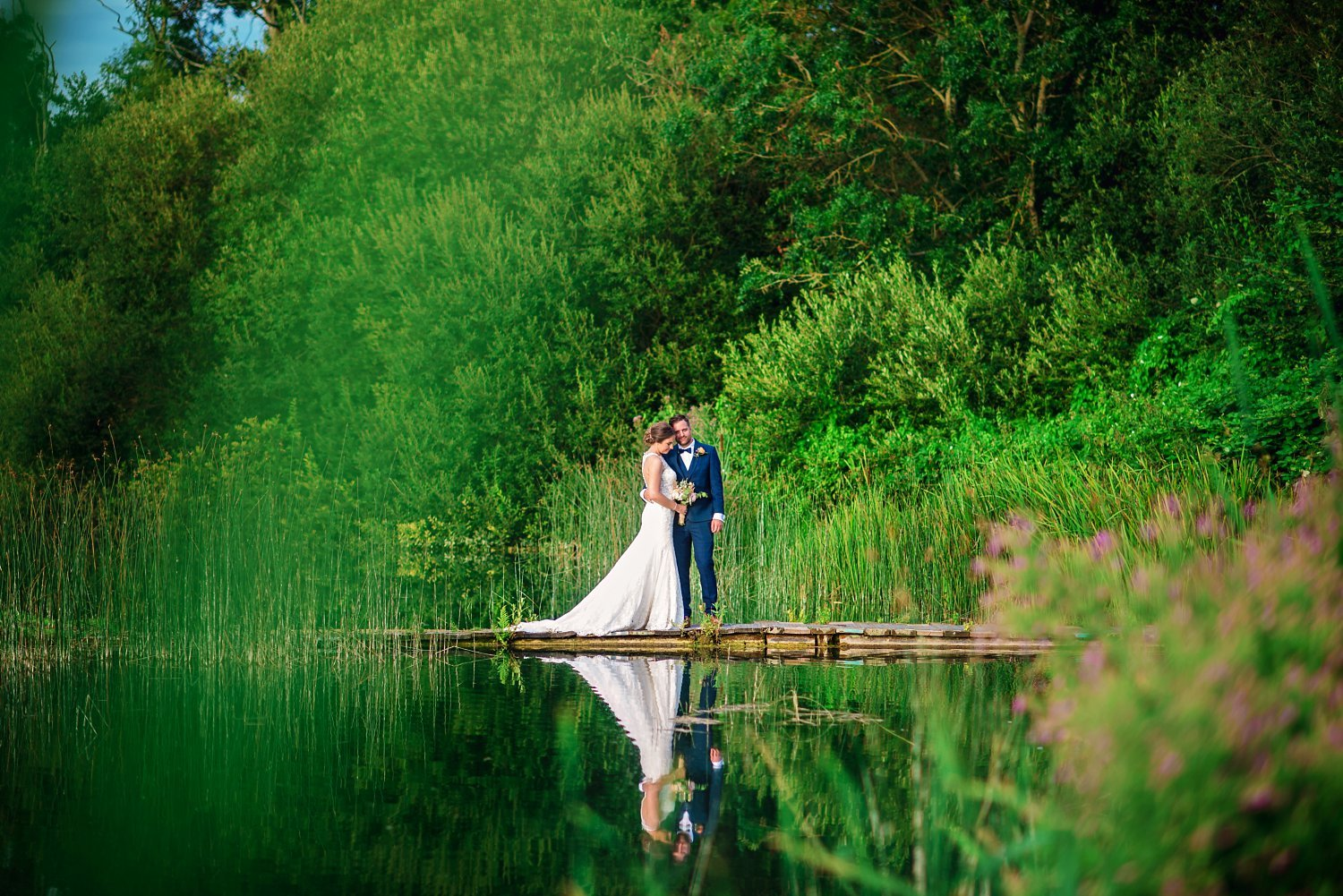 Duncton Mill Fishery Wedding - bride and groom. they are standing on the bridge