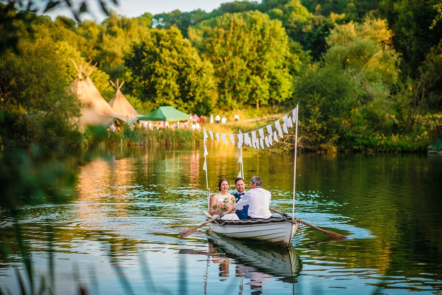 Duncton Mill Fishery Wedding - bride and groom are on the rowing boat.