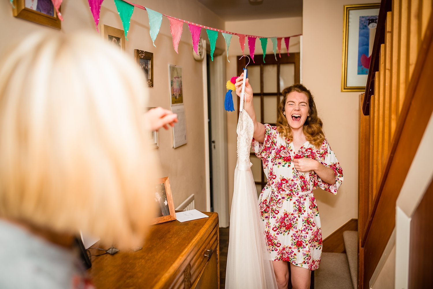 Farnham Wedding Photographer - bride to be is carrying her dress and laughing
