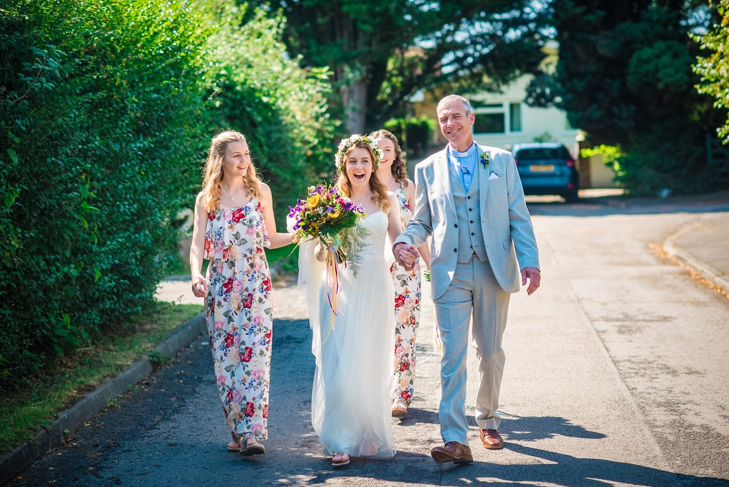 Farnham Wedding Photographer - bride is walking with her dad and sisters