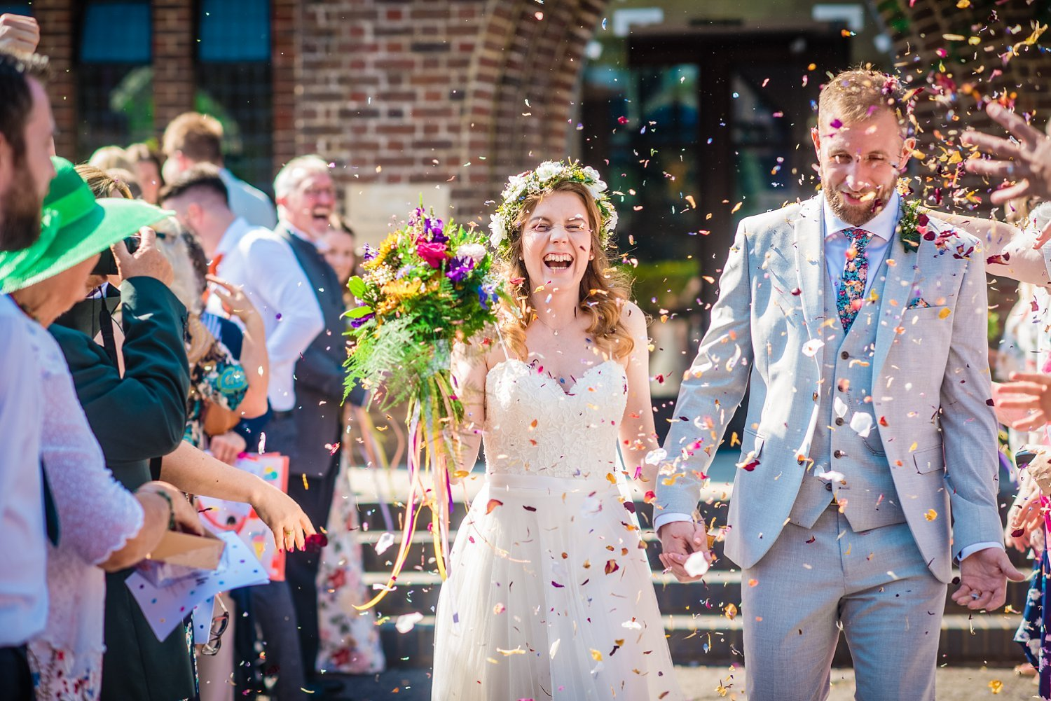 Farnham Wedding Photographer - husband and wife are walking while they are getting thrown confetti at them.. they are both happy and smiling