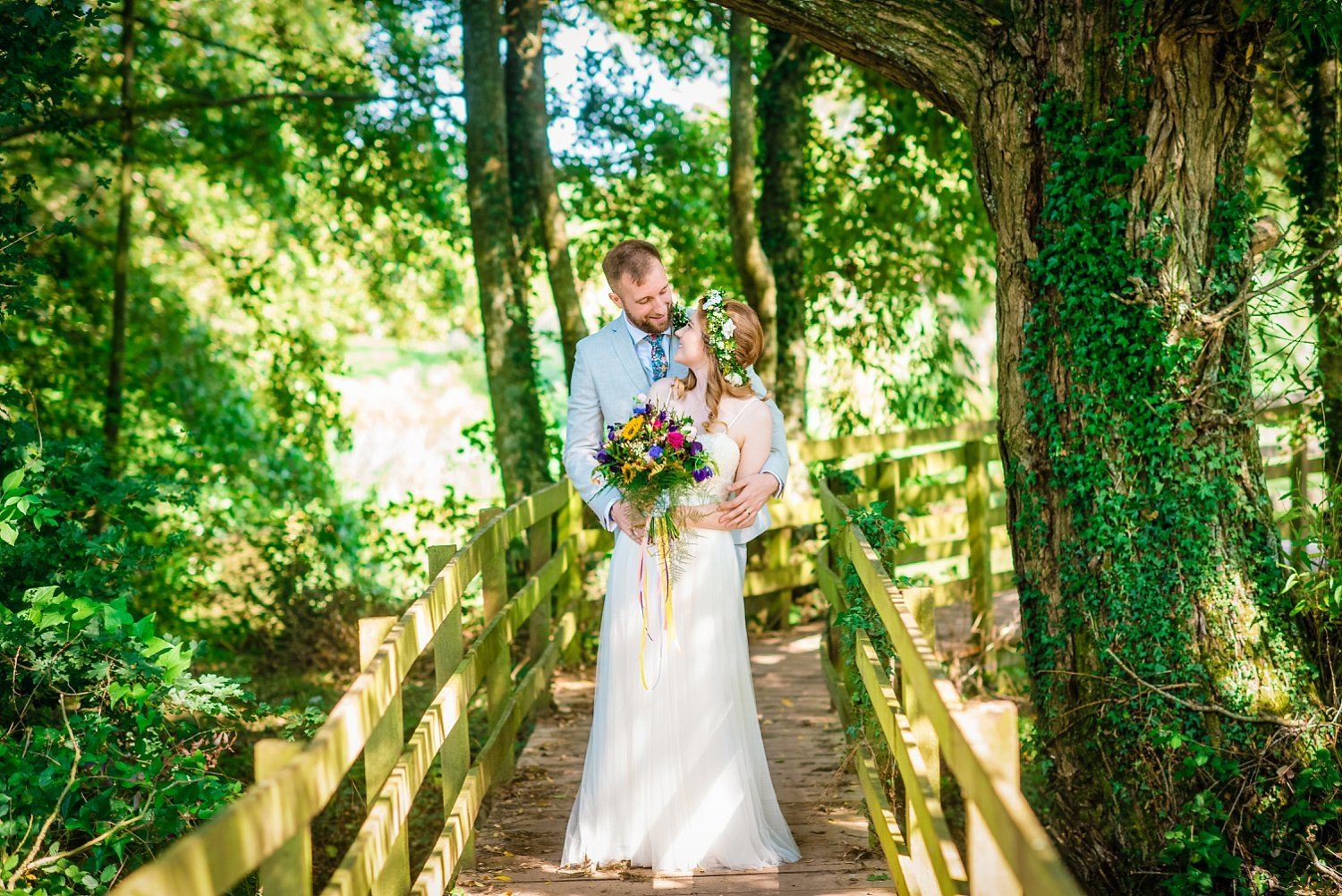 Farnham Wedding Photographer - groom is cuddling bride from behind, they are looking at each other. they are standing on the wooden bridge