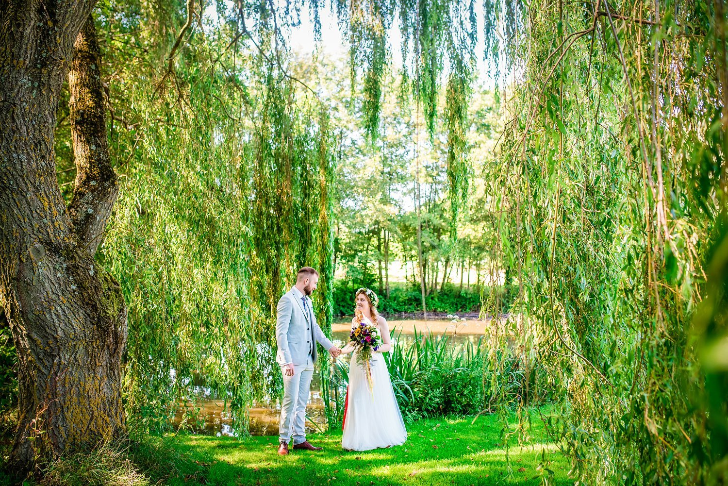Farnham Wedding Photographer - husband and wife under willow tree. they are holding hands