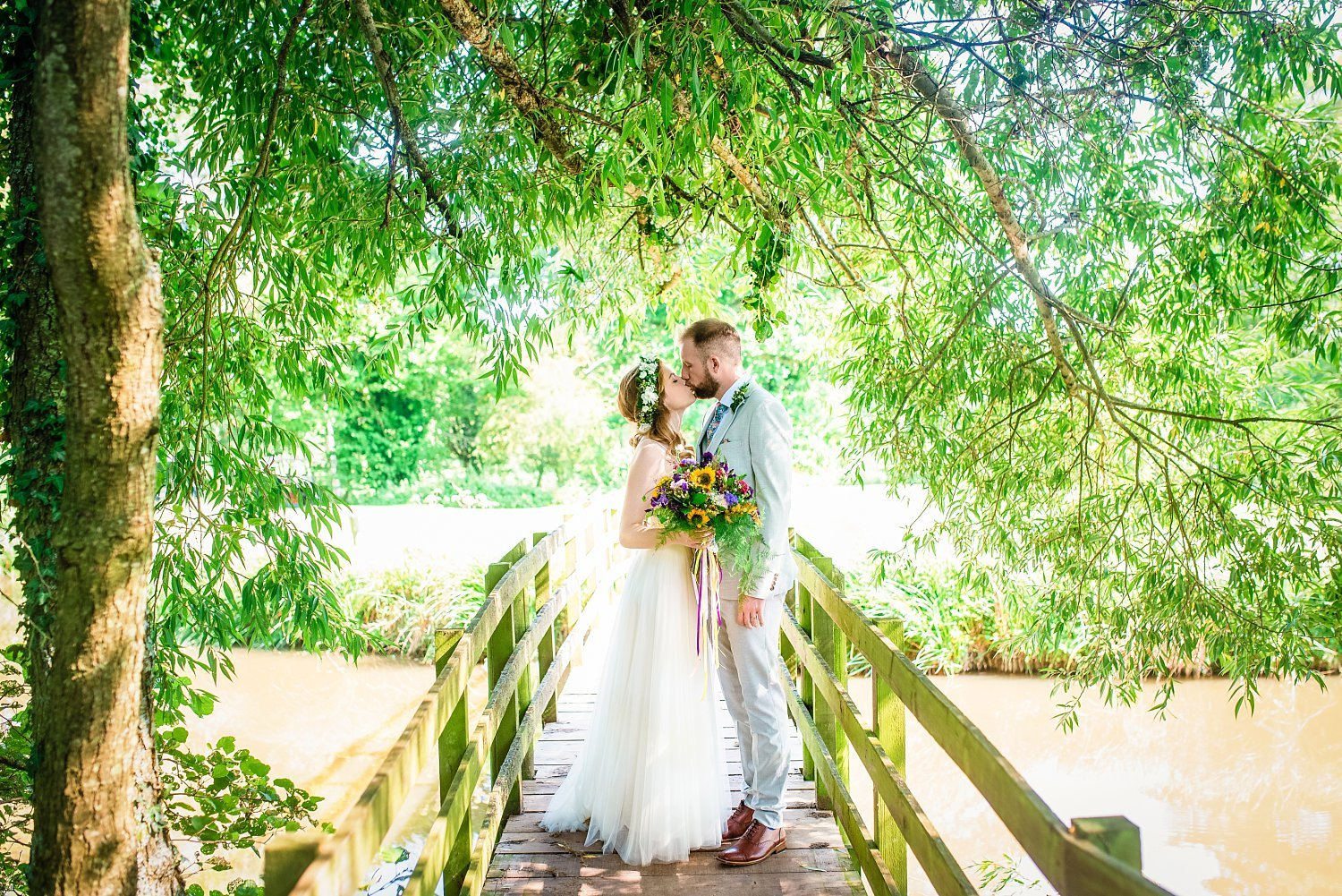 Farnham Wedding Photographer - bride and groom are standing on the wooden bridge. they are kissing