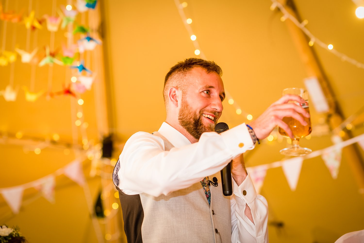 Farnham Wedding Photographer - groom is making a toast holding a beer in his hand
