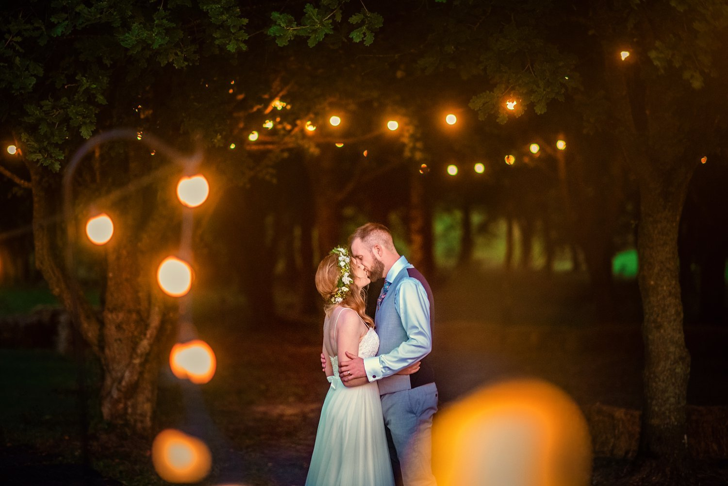 Farnham Wedding Photographer - husband and wife are kissing in the forest with fairy lights hanged on trees